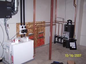 This photo shows the water-to-water unit with buffer tank and floor heat manifolds, notice the HRV in the upper left corner.